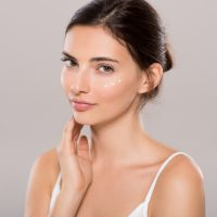 Young woman applying moisturizer on face isolated on grey background. Beautiful woman applying cosmetic cream on skin near eyes and looking at camera. Beauty and skin care concept.